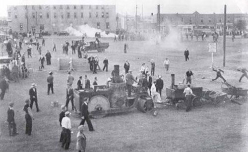 July 1, 1935: Regina Riot - Photograph of rioters and police during the Regina Riot.  Machinery at the bottom of the frame is the city's tar-making machine, parts of which were thrown at police during the riot (Source of photo - Wikipedia).