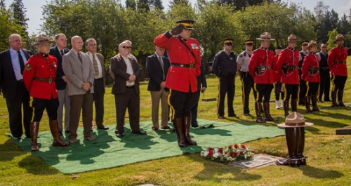 Photograph of Inspector Ted Dejager (OIC Mission Detachment) lays flowers and salutes the grave marker of Constable Kenneth Kornelson (Source of photo - Sheldon Boles).