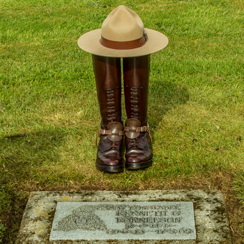 Photograph of RCMP stetson & high brown boots above the grave marker of Cst. Kenneth Kornelson (Source of photo - Sheldon Boles).