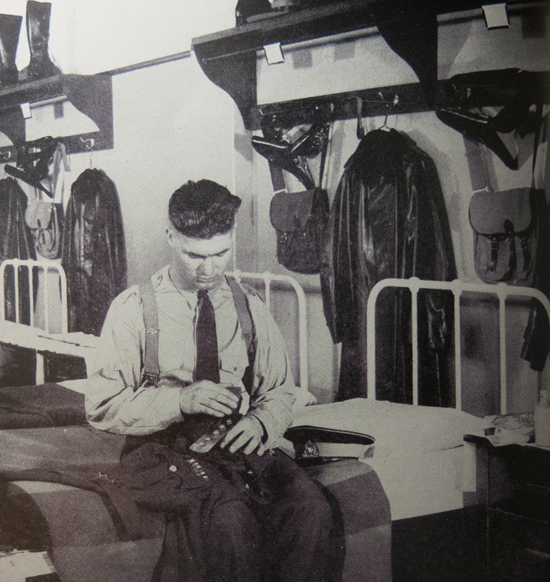 1946 - Photograph of RCMP  Recruit sitting on his barrack room bed polishing his brass buttons (Source of photo - RCMP Quarterly).