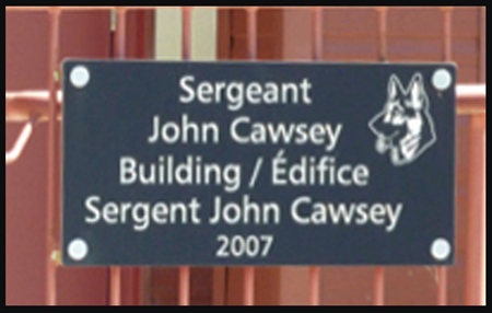 Photograph of the dedication plaque for the building at the RCMP Police Service Dog Training Centre in honour of the late Sergeant John Cawsey (Source of photo - Ric Hall's Photo Collection).