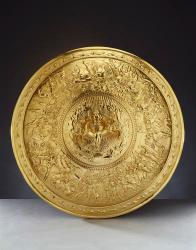 bouclier d'achille Il a été fondu à partir d'un dessin préparé par John Flaxman, lui-même inspiré par le texte de l'Iliade dans lequel Homère, au chant XVIII, fait une description précise du fameux bouclier