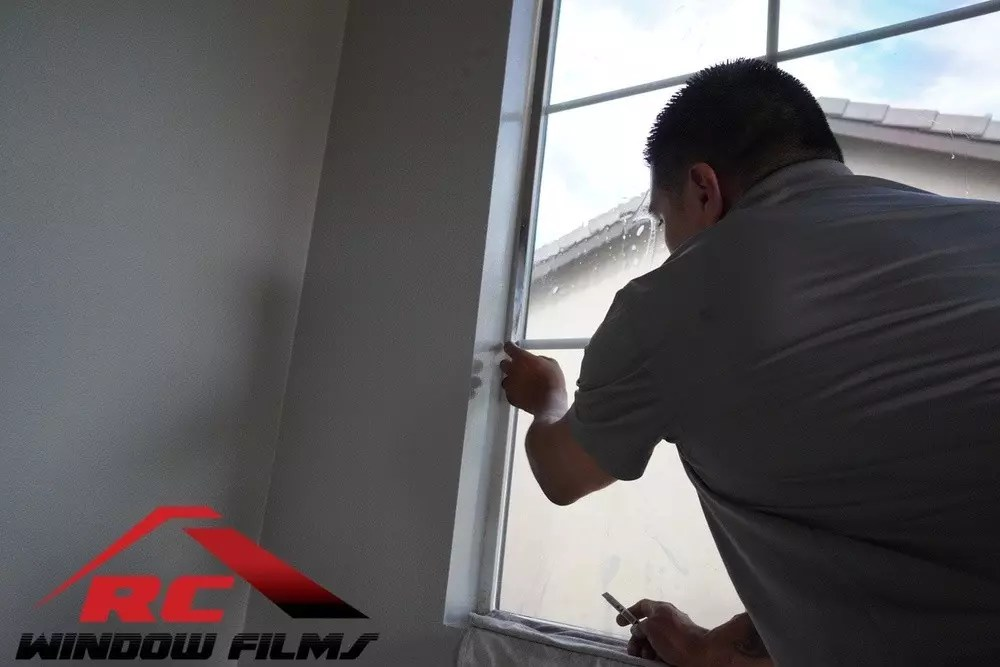 cutting home window tint to size during a home window tinting installation in menifee ca