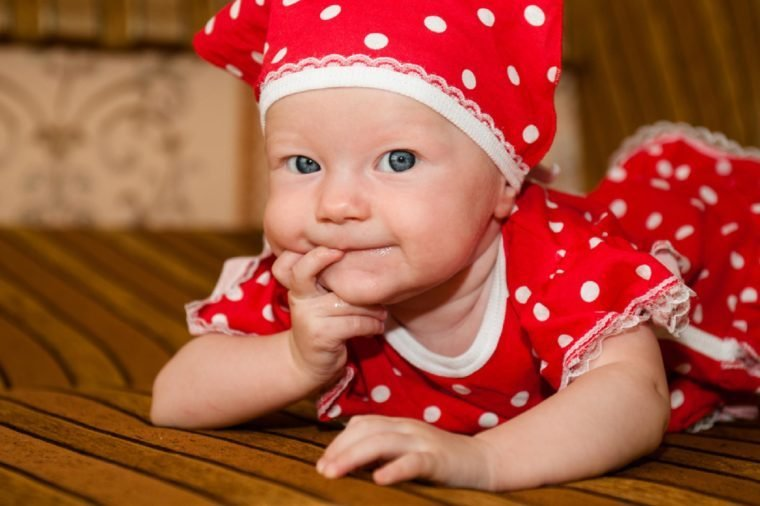 Beautiful expressive adorable happy cute laughing smiling baby infant face. Newborn child relaxing in bed. Nursery for young children. Family morning at home. funny child in a fashionable red dress