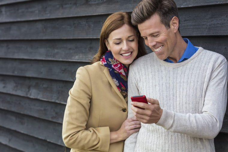 Attractive, successful and happy middle aged man and woman couple together outside using mobile cell phone
