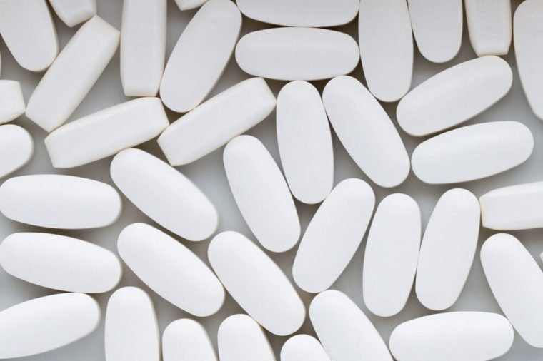 White pills on the white background.
