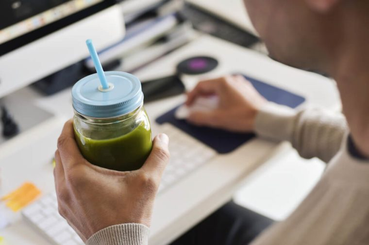 closeup of a young caucasian man drinking a green detox smoothie served in a glass jar at the office