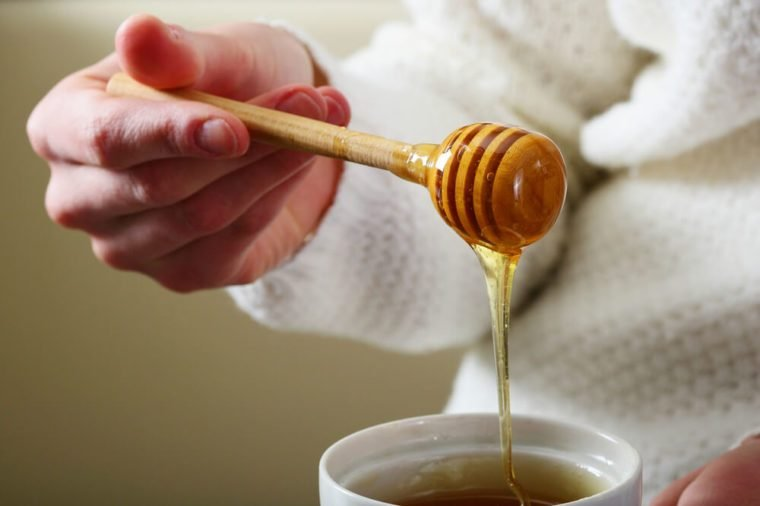 Spoon for honey with female hands