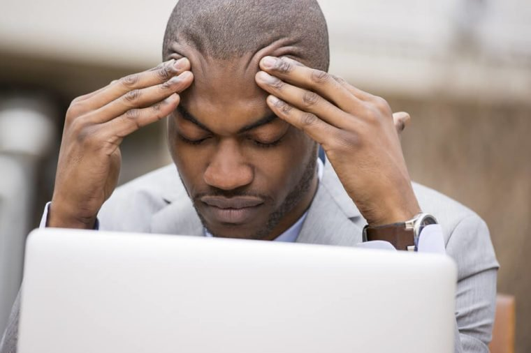 stressed young businessman sitting outside corporate office working on laptop computer holding head with hands looking down. Negative human emotion facial expression feelings.
