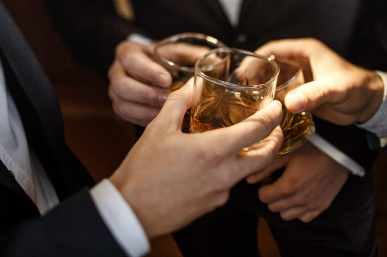 Multiethnic group of businessmen spending time together drinking whiskey and smoking, multicultural business team
