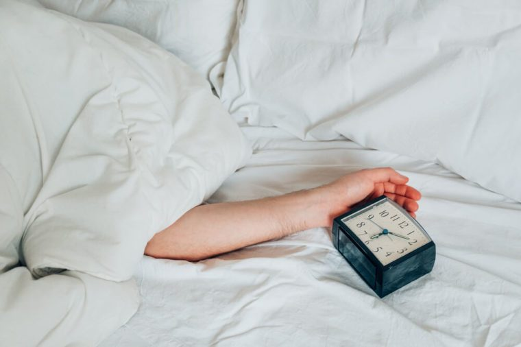 Laziness concept. Hand on a white bed sheet in the morning with alarm clock