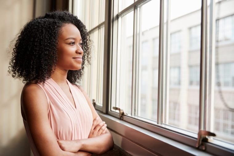 Young black woman with arms crossed looking out of window