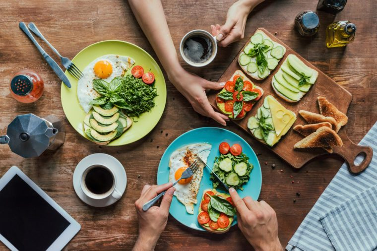 cropped shot of couple having healthy breakfast with vegetables and toasts