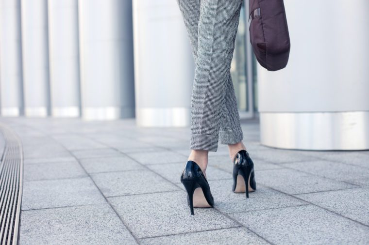 Close up of female legs of worker standing near her office. The woman is wearing formalwear and shoes on high heels. She is holding a handbag. Copy space in left side