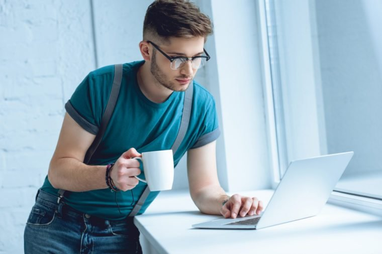 young man in eyeglasses holding cup of coffee and using laptop on windowsill