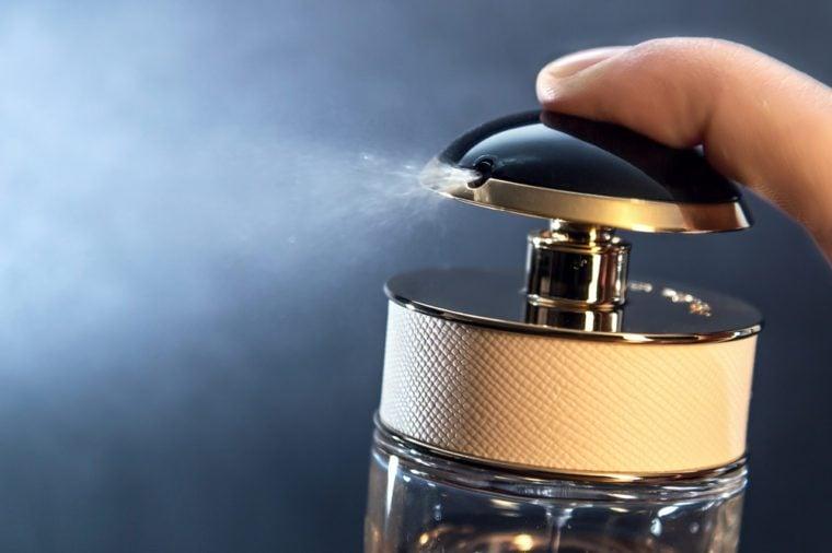 Close up of spraying perfume bottle on a dark grey background.