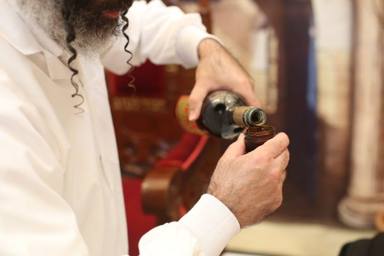 Rabbi holds kiddish cup with wine in front of Groom and Bride