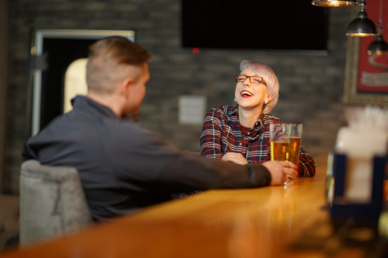 A happy girl, communicates in a bar with an man, drinks beer and laughs cheerfully. Indoors.