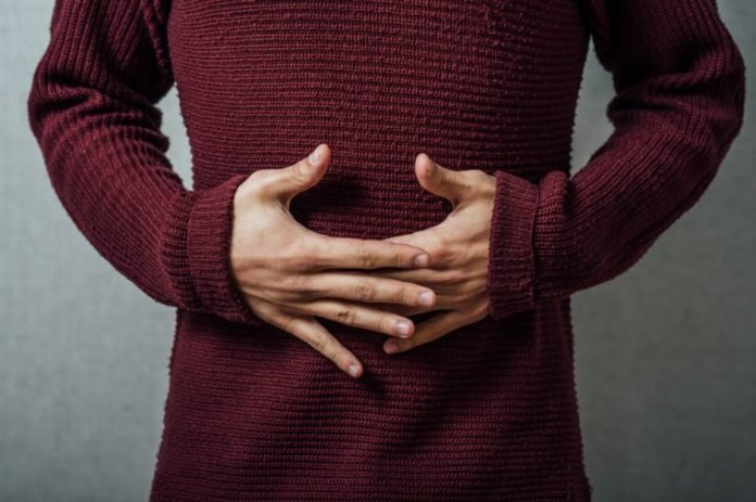 person holding their stomach in pain or indigestion