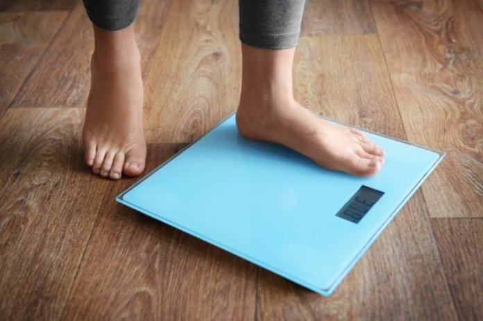 Female bare feet standing on a scales
