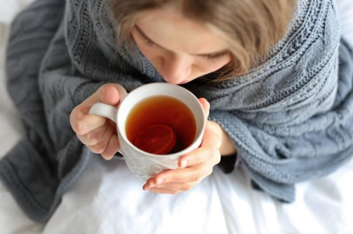 Young ill woman with cup of hot tea at home, closeup