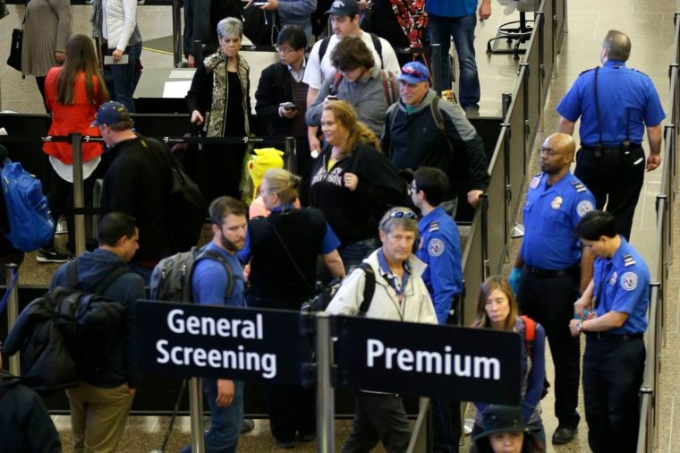 Travelers wait in line for security screening