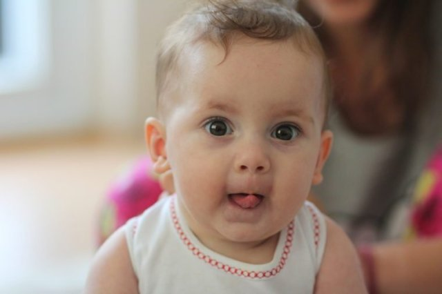 Little cute baby with tongue out.Weird funny face of a lovely cute baby
