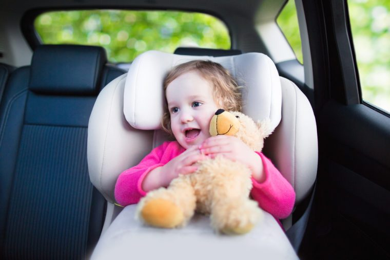 Cute curly laughing and talking toddler girl playing with a toy bear enjoying a family vacation car ride in a modern safe vehicle sitting in baby seat with belt having fun watching out of the window