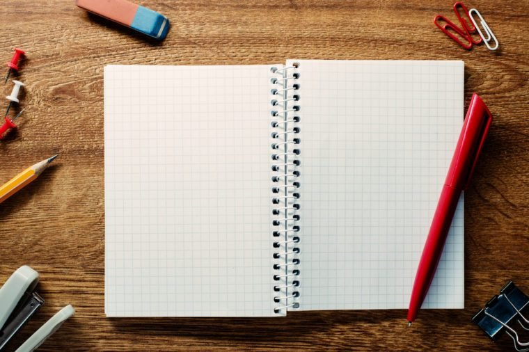 Red pen ready for writing on an open spiral notebook with blank pages with math pattern surrounded by school supplies on a wooden table, high-angle close-up