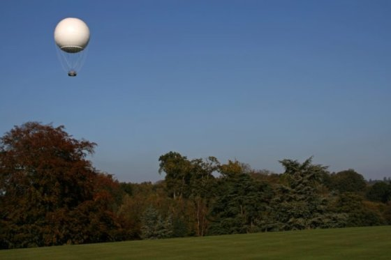 white weather balloon in the air above the trees