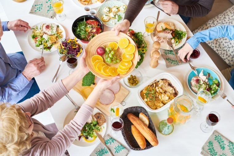 Top view of big happy family sitting at dinner table enjoying delicious homemade food during festive celebration and handing fruit plate across table