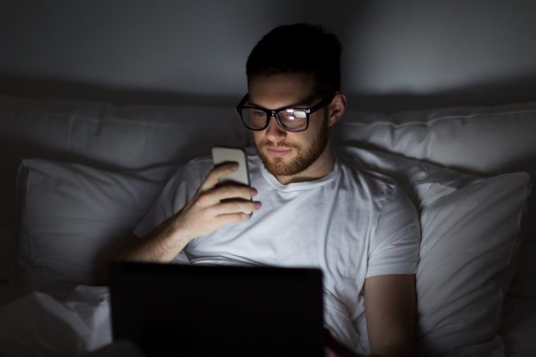 technology, internet, communication and people concept - young man in glasses with laptop computer and smartphone in bed at home bedroom at night