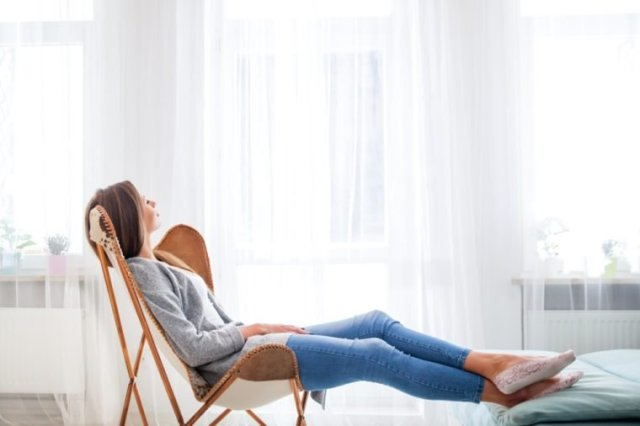 Young woman at home sitting on modern chair near window relaxing in living room