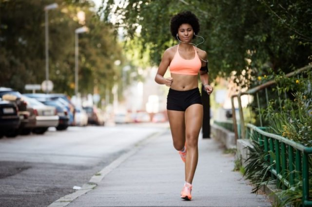 Healthy sportswoman running on sidewalk while listening to music.