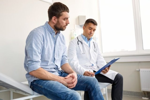 medicine, healthcare and people concept - doctor with clipboard and young male patient having health problem meeting at hospital