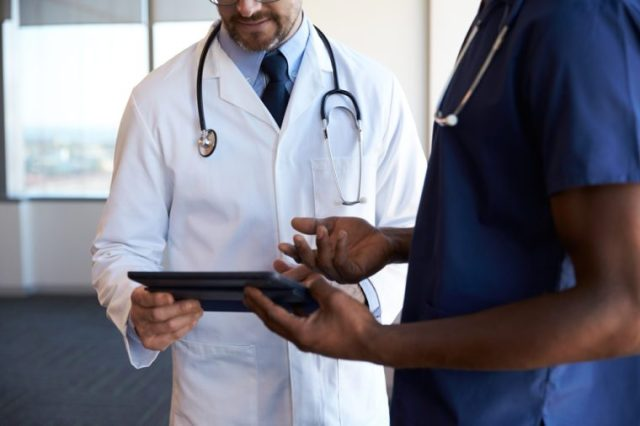 Close Up Of Hospital Staff Reviewing Notes On Digital Tablet