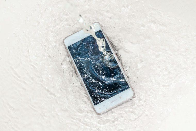 Phone in the water. Concept broken phone. Smartphone repair concept