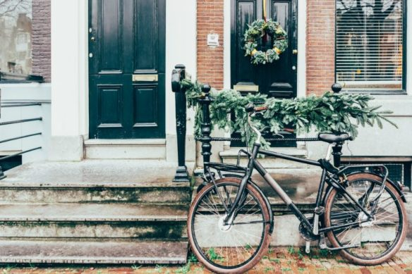 Cozy city picture, a bicycle parked at the entrance to the house decorated with Christmas tree branches.