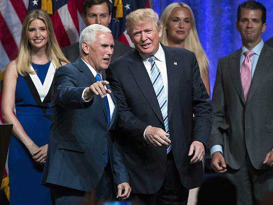 President Donald Trump and Vice President Mike Pence on stage Vice President Pence is speaking to the president and pointing something out,their families are behind them and all look very happy.
