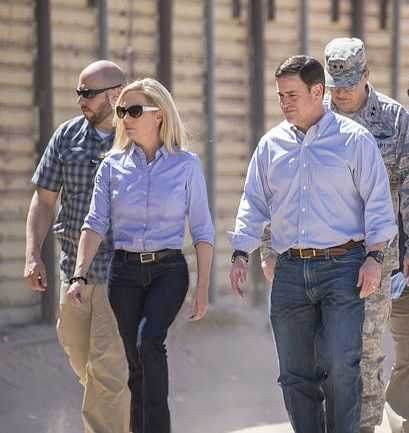 An image of Kirstjen Nielsen Inspecting The U.S. - Mexican Border it's a sunny day and she is wearing dark sunglasses which really sets off her lite blonde hair, she has blue jeans on and a blue casual collared shirt, the image is from head to lower calf, there are 3 men one to her left and 2 behind, one is dressed in army camo clothing the other 2 are also dressed casually.