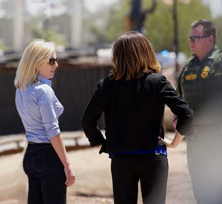 Another image of Kirstjen Nielsen inspecting the U.S. border she is wearing blue jeans and a light blue shirt, she has her back to the camera but turned to the right about 45 degrees which shows her perfect figure and golden hair.