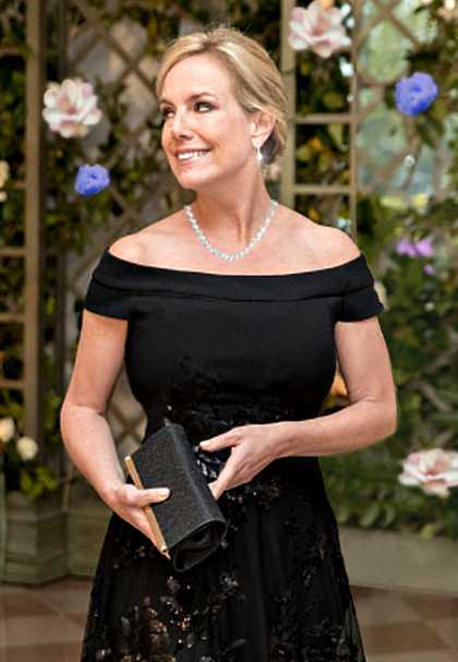 Kirstjen Nielsen, U.S. Secretary of Homeland Security is a picture of grace and beauty as she arrives for a state dinner at the White House, whe is wearing a black off the shoulder dress, her blonde hair is styled up, she is looking to the left and smiling.