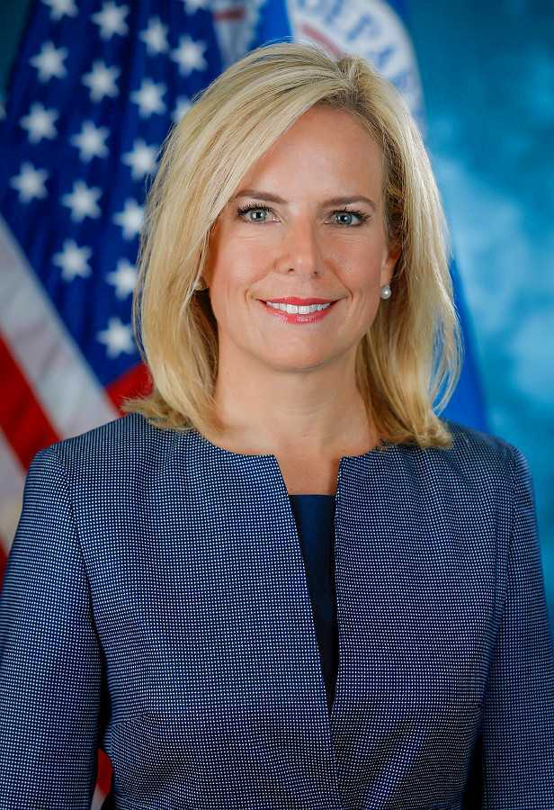 Official photo of homeland security secretary kirstjen nielsen, standing in from of an american flag it's a waist up image she is wearing a blue jacket and blue blouse her hair and makeup are perfect, she has lite blonde hair with large eyes and is smiling, she is a beautiful woman