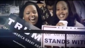 2 Black Female Trump Supporters holding up pro-trump signs, smiling wide and cheering at a Rally