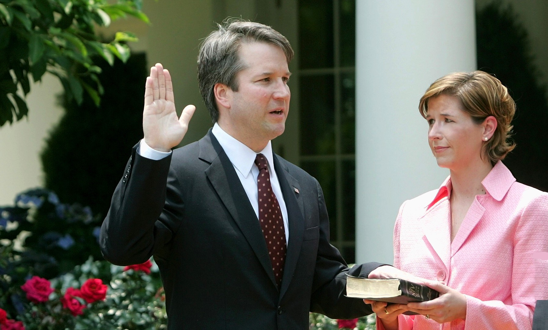 Brett Kavanaugh and Ashley Kavanaugh at the swearing in to the United States Court of Appeals for the D.C. Circuit Brett has his left hand on the bible Ashley is holding and he has his right hand raised he is in a dark suite and burgandy tie and Ashley is wearing a pink skirt suit, she looks very attractive.