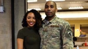 an image if a black man and woman, he is a sergeant in the army, they are both facing the camera and smiling, he is wearing his green fatigues and she is wearing a green sweater, they are both attractive people.