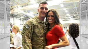 image of an army captain holding her around the waist he has a sly smile on his face and is wearing his green fatigues, she is wearing wearing a red dress. She is very attractive with her long brown hair and smile.