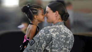 Image of a female army captain rubbing noses with her 4 year old daughter, she is wearing green camouflage clothing.