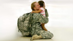 image of a woman coming home she is dresses in her army fatigues and she went to her knees to hug her child she is weeping hard.