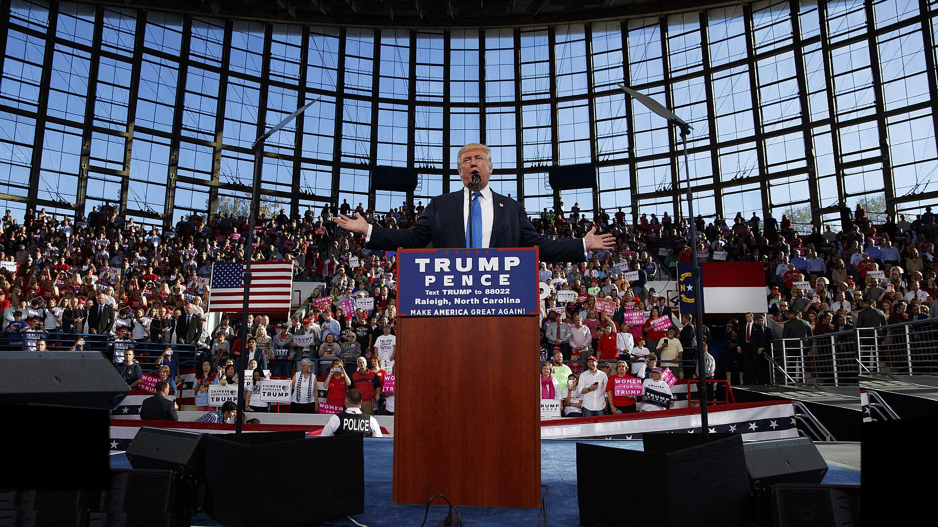President Trump has a huge rally in Raleigh, South Carolina, he is standing at a podium facing the camera arms spread wide the crowd behind him is going wild they are seated in front of a giant glass wall, it looks awesome